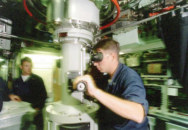 """A Petty Officer on board the attack submarine USS Pasadena (SSN 752) in the Pacific Ocean conducts a periscope sweep to ensure that no """"contacts"""" exist that would interfere with surfacing. (U.S. Navy photo by Photographer's Mate 2nd Class August Sigur. July 19, 1998)"""