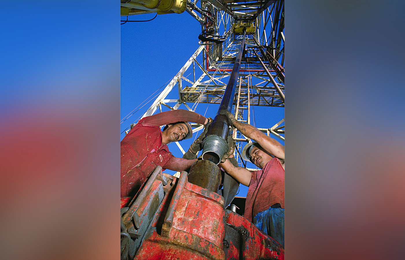 The drilling crew attach a piece of drillpipe hanging from the derrick (the tall structure) to the drillstring that is already below the ship (the top of the drillstring is the brown metal piece sticking above the red structure).