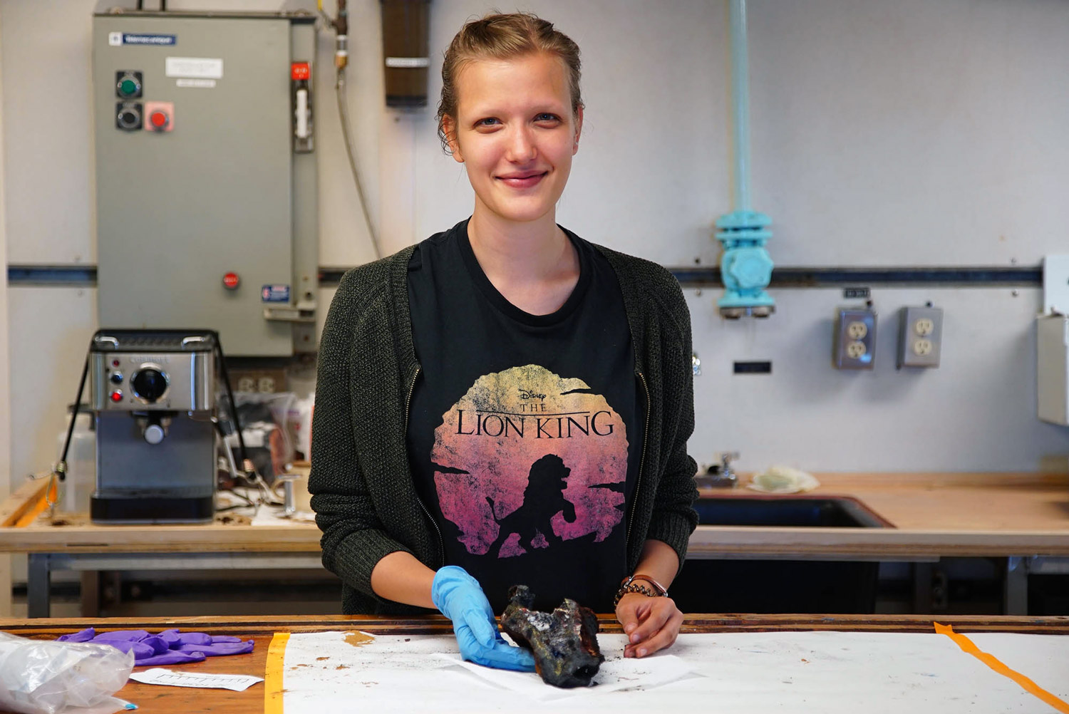 Vanessa Schenker with a hydrothermal vent chimney sample in the lab on board R/V Thomas G. Thompson. (Photo by Erik Olsen)