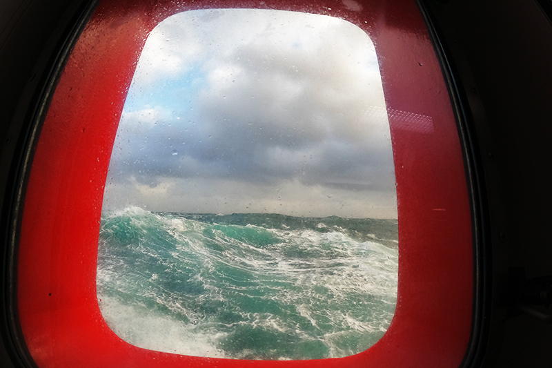 A view from one of the porthole windows in the main lab shows the rough conditions outside. Photo by Marley Parker, @Woods Hole Oceanographic Institution