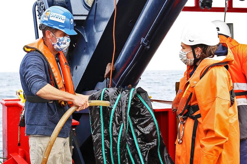 Co-lead scientist Joel Llopiz and guest student Helena McMonagle discuss protocol for rinsing the MOCNESS nets on the aft deck. Photo by Michelle Cusolito, @Woods Hole Oceanographic Institution