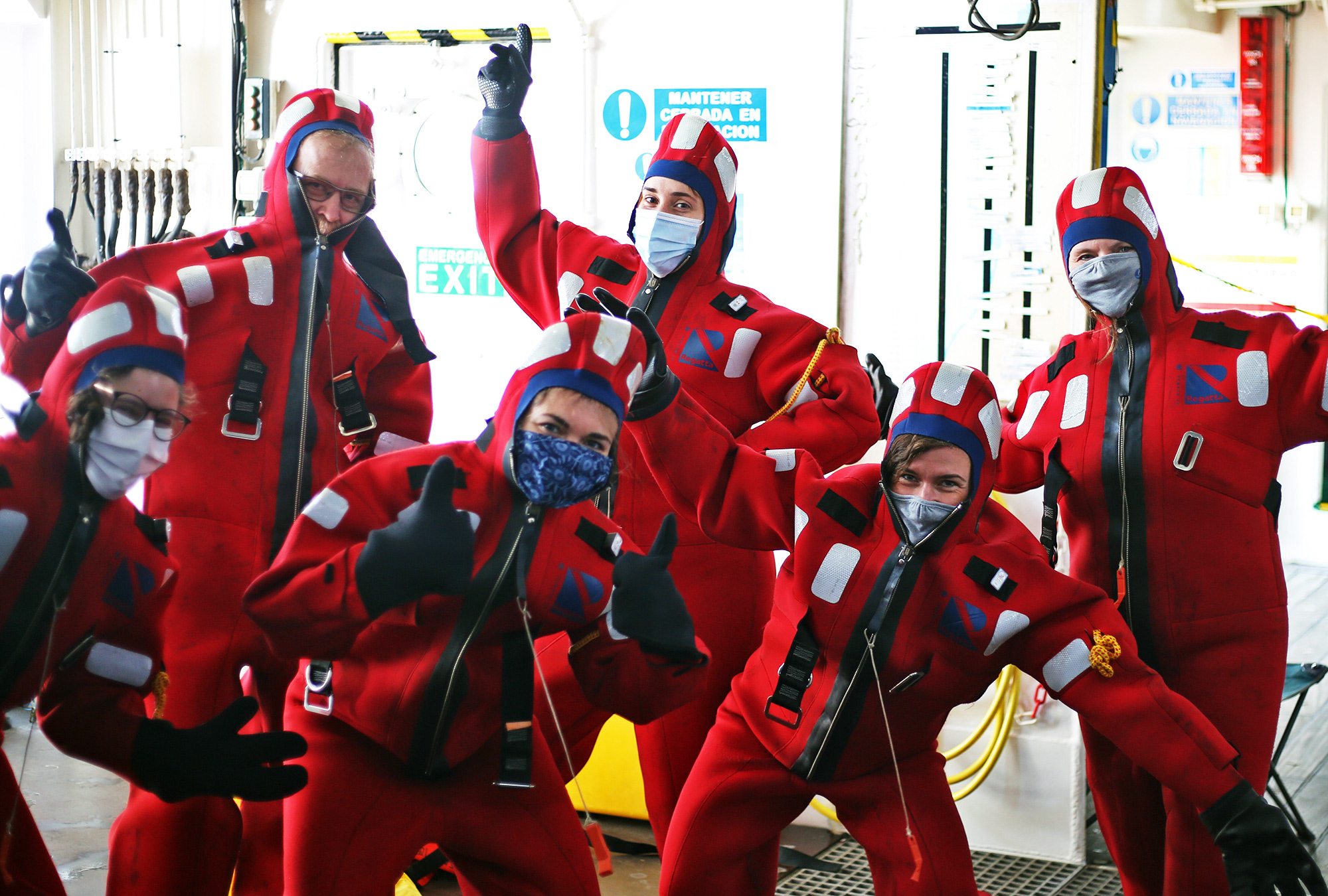 Members of the science team don immersion suits during the safety training.
