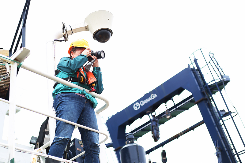 Michelle Cusolito photographs equipment tests on the aft deck of the Sarmiento de Gamboa. Photo by Marley Parker, @Woods Hole Oceanographic Institution