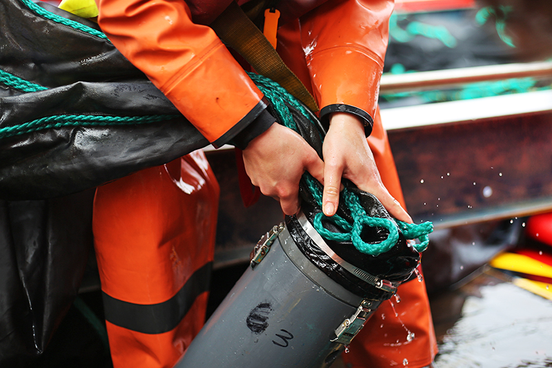 Julia Cox detaches a MOCNESS net from a cod end bucket. Photo by Marley Parker, @Woods Hole Oceanographic Institution