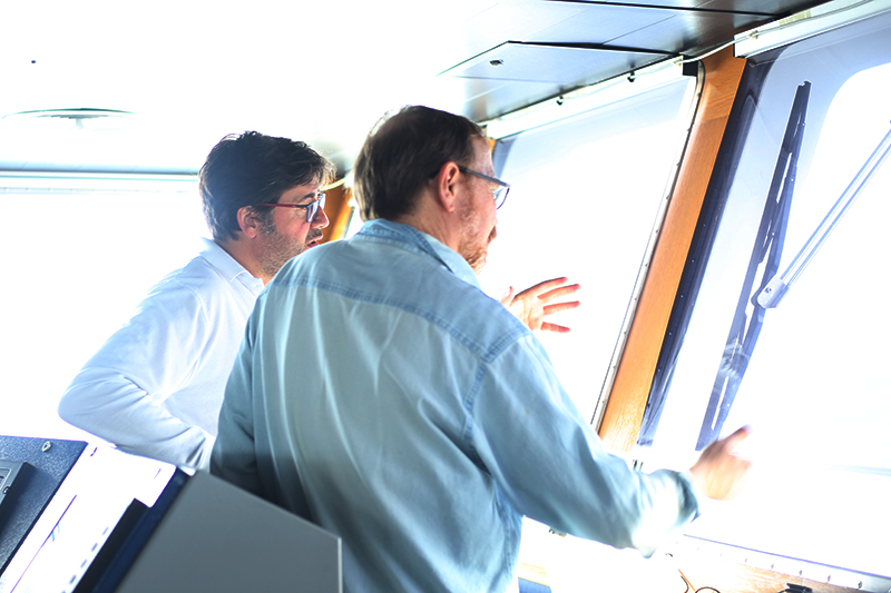 Captain Miguel Ángel Menéndez Pardiñas and co-lead scientist Ken Buesseler discuss operations on the bridge. Photo by Marley Parker, @Woods Hole Oceanographic Institution