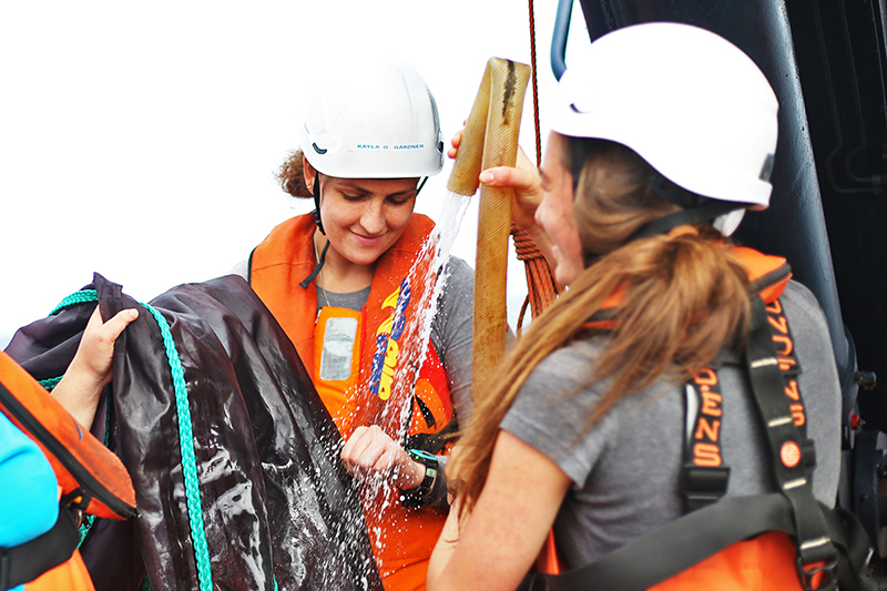 Kayla Gardner and Julia Cox rinse a MOCNESS net. Photo by Marley Parker, @Woods Hole Oceanographic Institution