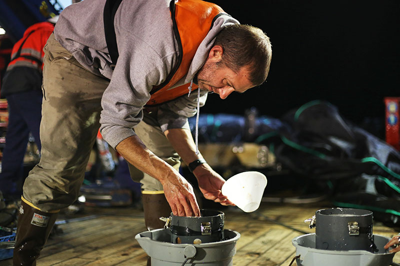 Joel Llopiz examines a fresh sample from MOCNESS on the aft deck. Photo by Marley Parker, @Woods Hole Oceanographic Institution