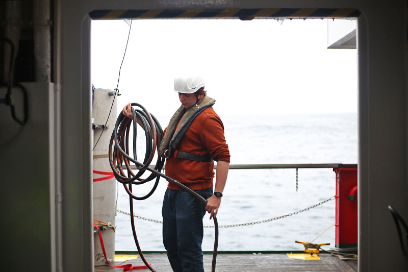 John San Soucie coils a hose on the deck of the Sarmiento de Gamboa. Photo by Marley Parker, @Woods Hole Oceanographic Institution