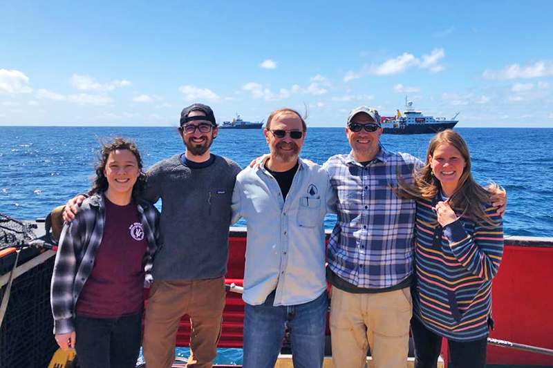Erin Frates, Jackson Sugar, Ken Buesseler, Justin Ossolinski, and Jessica Kozik gather on the aft deck for a photo featuring the other ships. Photo by Marley Parker, @Woods Hole Oceanographic Institution