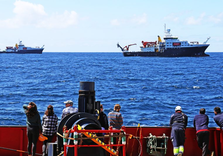 Members of the science team and crew aboard the Sarmiento de Gamboa gather to wave and take pictures of the RRS Discovery and the RRS James Cook during a coordinated rendezvous in the North Atlantic. Photo by Michelle Cusolito, @Woods Hole Oceanographic Institution